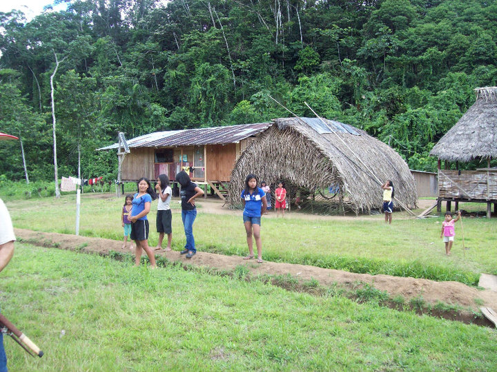 We're standing on the runway. A traditional hut is seen in the background.